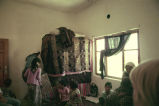 Women and children in a room looking at a storage area covered by a blanket