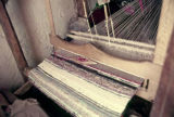 Shuttle lying on striped plain weave on a heddle loom
