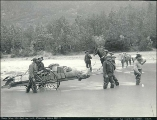 Fording Dyea River with cart full of supplies on the Chilkoot Trail, Alaska, 1897.