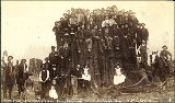 Group of people seated on and around large cedar stump, 60 feet in circumference, Sedro Woolley,...