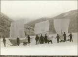 Klondikers crossing frozen Lake Laberge with boats and sleds outfitted with sails, Yukon...