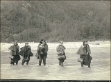 Actresses fording Dyea River on the Chilkoot Trail, Alaska, 1897.