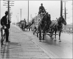 Automobiles and horse drawn wagon hauling lumber, W. Spokane St., Seattle, Washington, June 29,...