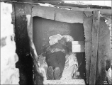 Homeless man lying in makeshift bed in shack in shantytown known as Hooverville, Seattle,...
