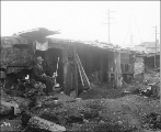 Homeless man sitting in front of shack in shantytown known as Hooverville, Seattle, Washington,...