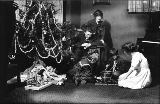 Family, three children and two adults, celebrating Christmas with tree and presents, Seattle,...