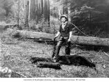 Lawrence D. Lindsley with gun standing over dead bear and two cubs, location unknown, probably...