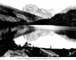 Man admiring reflection of Bonanza Peak in Lyman Lake, September 26, 1919