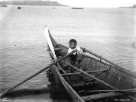 Makah Indian boy rowing a canoe at Neah Bay, ca. 1900