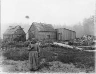 Quinault woman standing on beach in front of house between Taholah and Queets, Quinault...