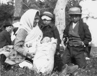 Woman, infant in cradleboard and two boys (possibly Tlingit) on an outing, Alaska, ca. 1913