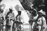 Spokane & Colville women pose in ceremonial dress by tepee