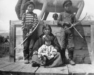 Gitksan woman and children posed by totem of a cougar, Kitwanga, British Columbia, 1910