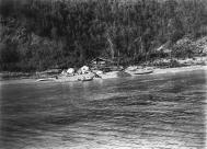 Tlingit canoes pulled up on beach by camp, Yakutat, Alaska, ca. 1894