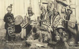 Chilkat dancers pose in ceremonial dress with wood carvings, Alaska, 1895