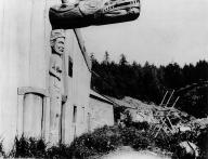 Nootka totem pole stands against house, British Columbia, 1903.