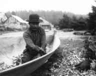 Quileute man named Talicas Eastman making a canoe, Quileute Reservation, Washington, 1905.