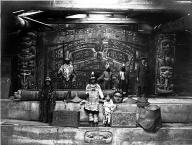Chilkat carvings in Koh-Klux's big house with men & children in ceremonial dress, Klukwan,...