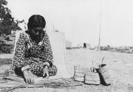 Makah woman named Mary Jackson, sits outside on mat weaving baskets, Washington, 1905.