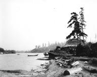 Salmon Bay Charlie's house at Shilshole with canoe anchored offshore, ca. 1905