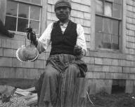Quileute man named Dickson Paine sits holding shell rattle, Quileute Reservation, Washington, 1905.