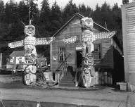 Kwakiutl totem poles and house belonging to Nimpkish Chief Tlah-Co-Glass, Alert Bay, British...