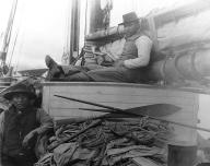 Aleut seal hunters on board ship with hunting equipment, Alaska, ca. 1898