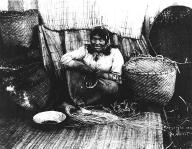 Puyallup woman weaving baskets, Washington, 1900.