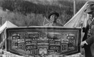 Chilkat man stands behind woven blanket, Alaska, ca. 1925
