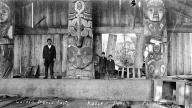 Haida man and boys stand inside Chief Soni-Hat's house, Kasaan, Alaska, 1914.