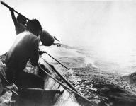 Charles White in canoe get ready to harpoon a whale off the coast of Washington, ca. 1930