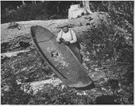 Quinault man using plane to smooth side of canoe near Lake Quinault, Washington