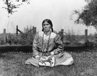Yakama woman named Retta Billy seated on grass with bag, Washington, 1909.
