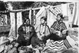 Cayuse women in beaded clothing pose with beaded and woven objects