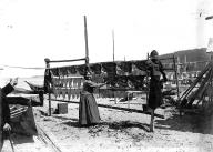 Makah woman and fish drying on a rack, Neah Bay, ca. 1900