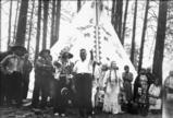 "San Poil chief Jim James in ceremonial dress stands with others by his tepee at the ""Ceremony..."