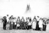 Plateau region men women & children from the Columbia River area pose by tepee