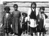 Salish children pose by wooden house, Montana