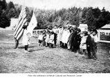 Children on the Makah Indian Reservation saluting the U.S. and a Christian flag
