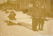 Three children at play with a sled in Dawson, Yukon Territory, ca. 1900.