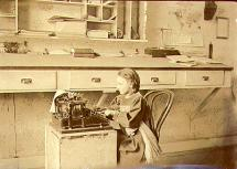 Flora Holmes, daughter of Captain William Holmes of the steamboat COLUMBIAN at a typewriter in the...