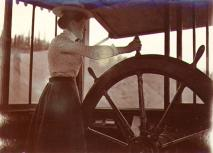 Mabel Meed at the wheel of the steamboat PROSPECTOR during a trip up the Pelly River, Yukon...