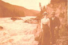 William and Mabel Meed standing on the bank of the Stewart River at Fraser Falls, Yukon Territory,...