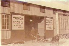 Two men with dogsled in front of the Yukon Dock Company office, Dawson, Yukon Territory, ca. 1900.
