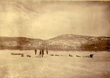 Two women and two men with dogsleds on frozen Lake Laberge, Yukon Territory, April 1902.