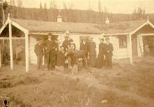 William and Mabel Meed with group of people feeding a moose calf outside of a North-West Mounted...