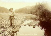 Prospector with shovel and gold pan at the edge of a creek, Yukon Territory, ca. 1898.