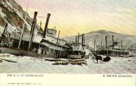 Postcard depicting the Northern Commercial Company steamboats in winter quarters at Steamboat...