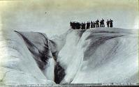 Excursion party posing at the edge of a crevasse in Muir Glacier, Alaska, 1895.