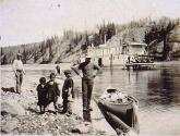 Indian children and Klondikers with canoe on the shore of the Yukon River with steamboat GOLD STAR...